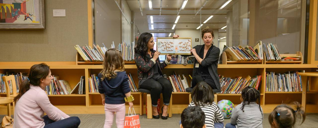 Image of two women reading stories to children at The Met