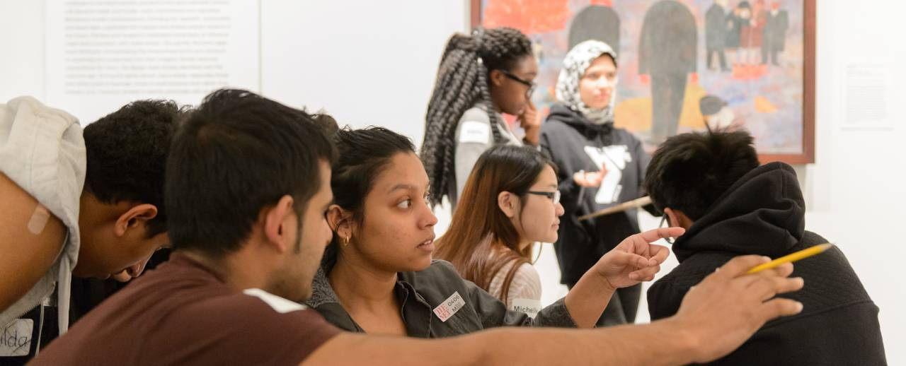 Image of young adults taking part in a discussion and pointing towards an artwork