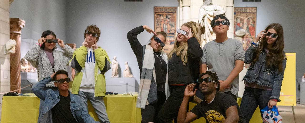 Image of multiple teens in an exhibition space wearing sunglasses and posing for a picture