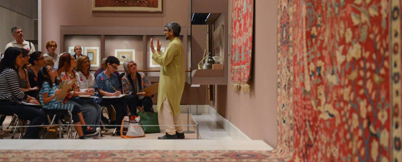 Image of a man talking in front group with clipboards inside gallery hanging with tapestries
