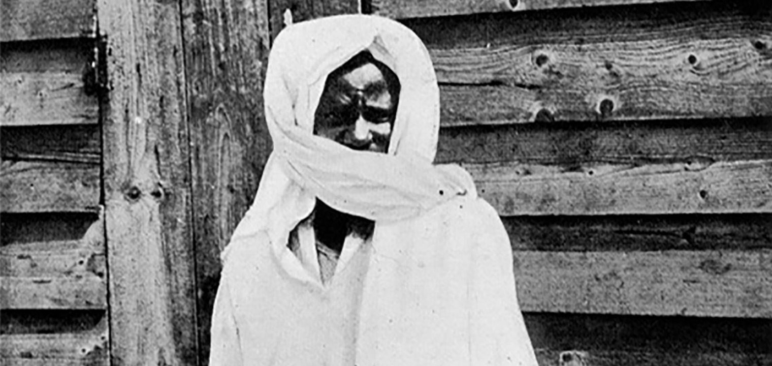 A black-and-white photo of a man shrouded in all-white cloth