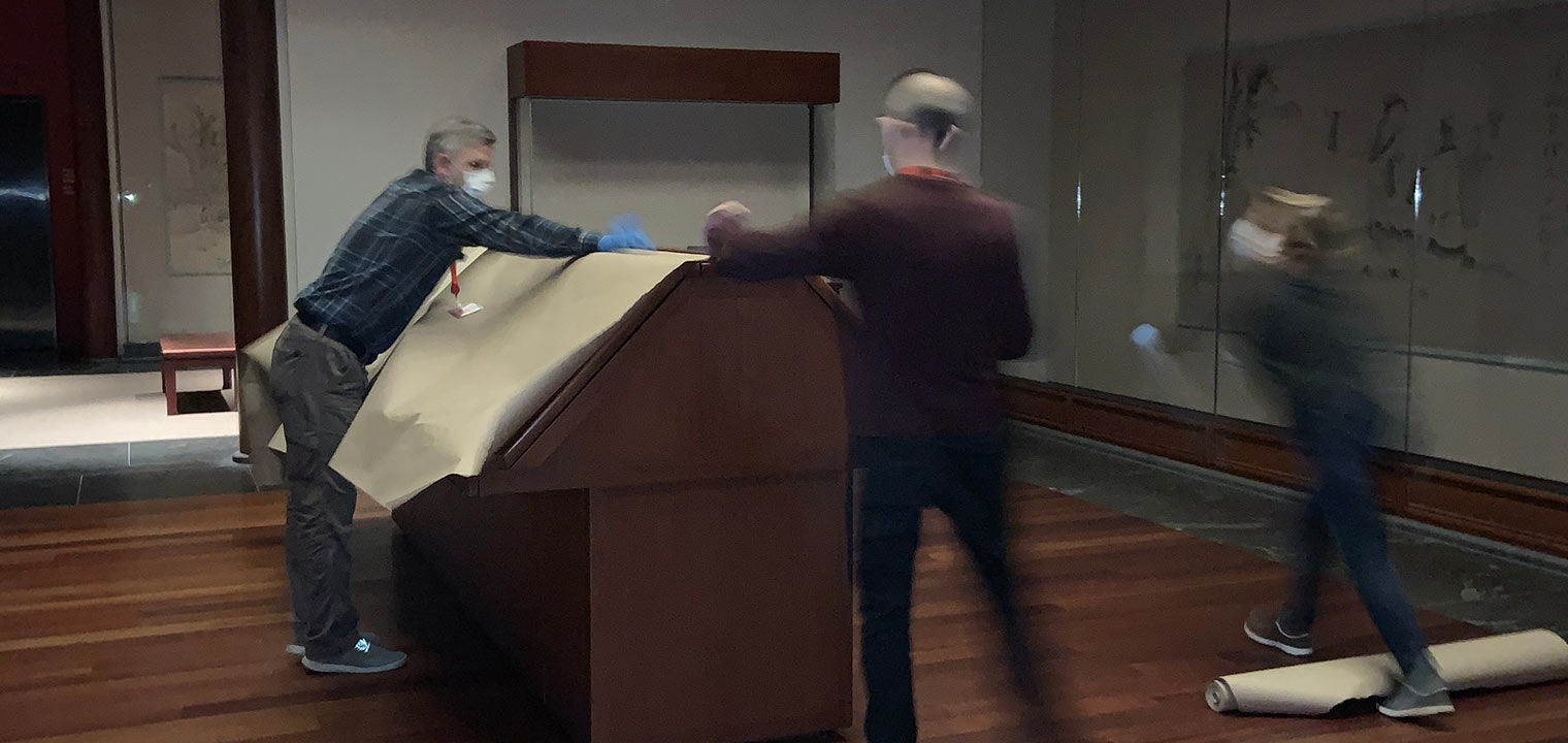 Three people wearing gloves and face masks set butcher paper over a case in the middle of an art museum gallery