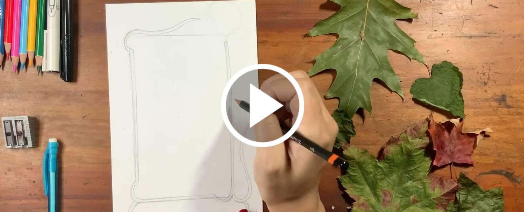 Video still: Colored pencils, paper, leaves and a hand holding pencil ready to draw.