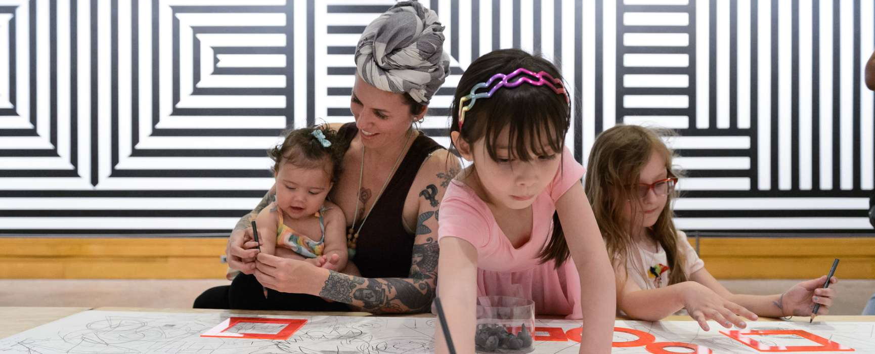 Image of a woman and three children work on an art project.