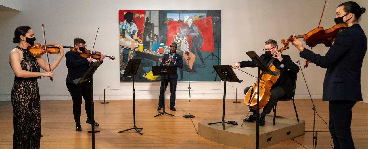 Musicans performing in a gallery.