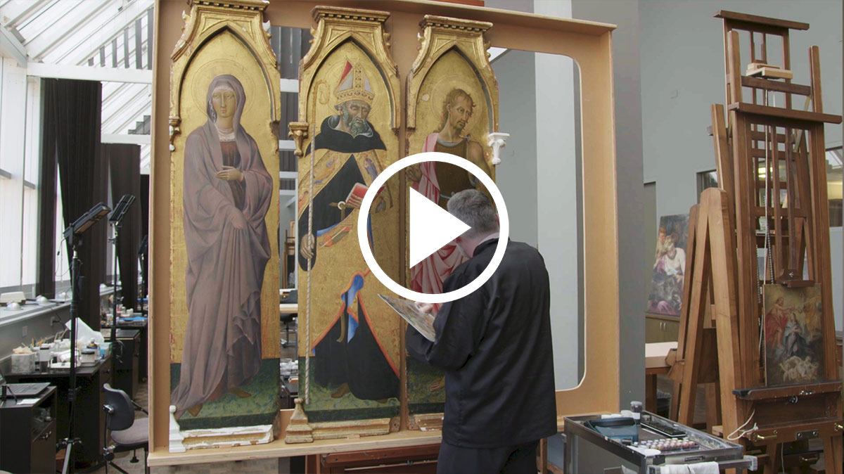A conservator working on a large golden altarpiece.