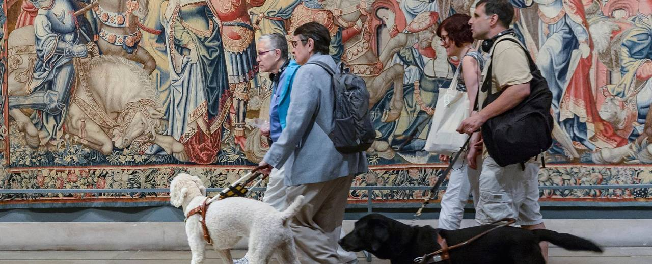 A group walks through the museum with two guide dogs.