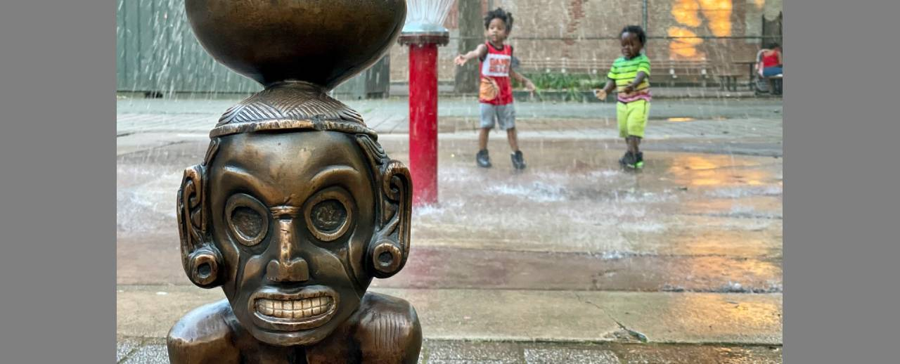 Children play in a water fountain next to a sculpture.