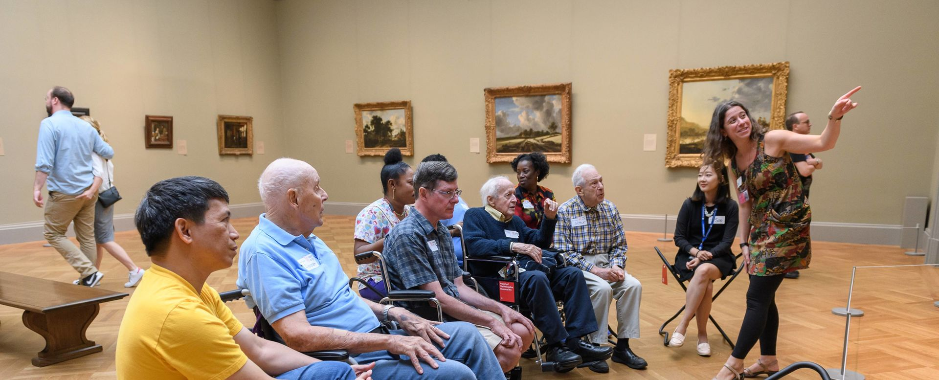 A group sitting in a gallery listen to a woman speak about an artwork.