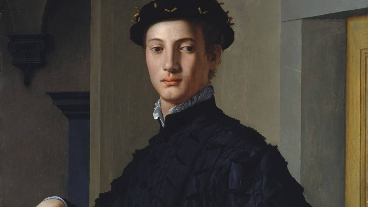 A young man looking aloofly in the direction of the viewer poses within a bare and enigmatic architectural interior.