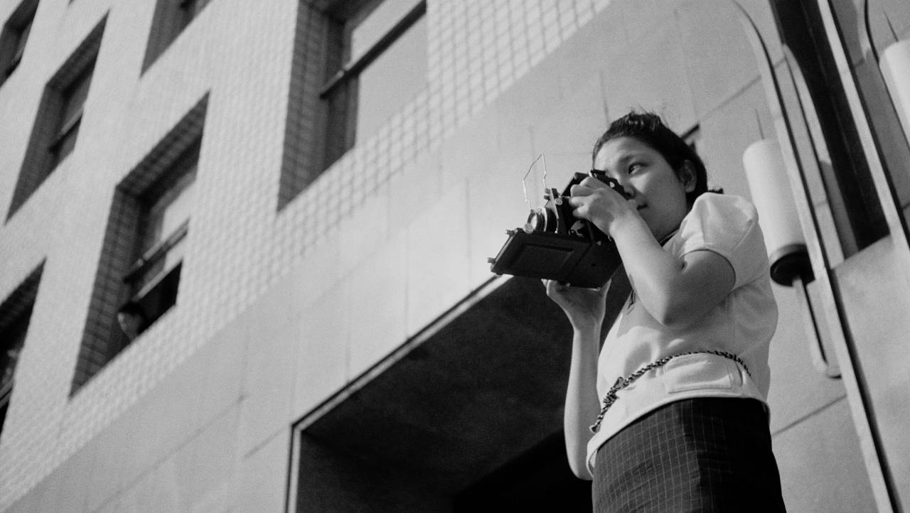 A black and white photograph of a young woman taking a photograph with a camera.