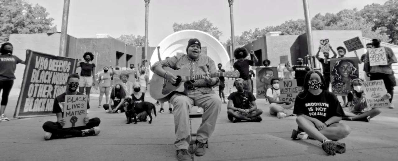 Black and white image of artists, activists, scholars, students, and community leaders standing and sitting holding protest signage. A man sitting in a chair with a guitar is in the center.